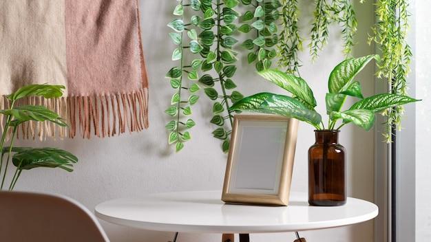 Bijgesneden opname van biophilia-vrijetijdshoek met mock-upframe, salontafel en kamerplanten
