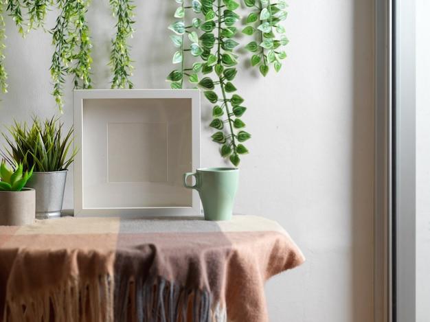 Bijgesneden opname van biophilia-vrijetijdshoek met mock-upframe, salontafel, mok en kamerplanten