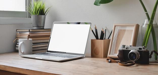 Bijgesneden opname van comfortabele werkruimte met laptop met leeg scherm, kantoorbenodigdheden en camera
