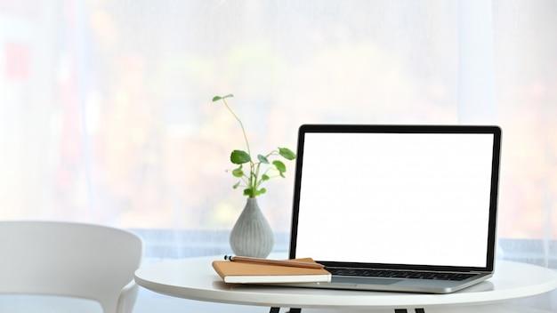 Bijgesneden opname van computer laptop met wit leeg scherm samen met potplant, notebook en potlood op de moderne tafel met comfortabele woonkamer als
