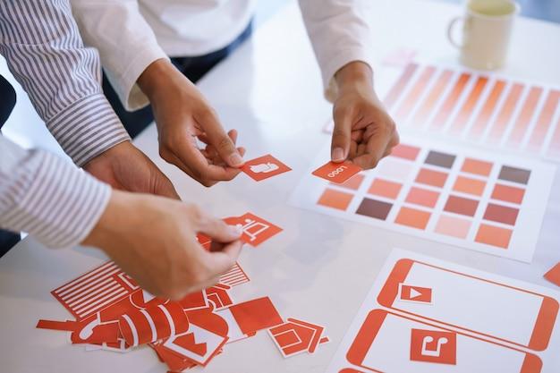 Bijgesneden opname van creatief ux ui-ontwerpteam ontwerpen, mobiele applicatie ontwikkelen op basis van prototypes en draadframe-layout. mobiele applicatie ontwikkelaar werkplekconcept.