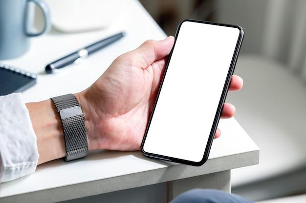 Bijgesneden opname van de hand van de man die een smartphone met een leeg scherm vasthoudt terwijl hij aan tafel zit.