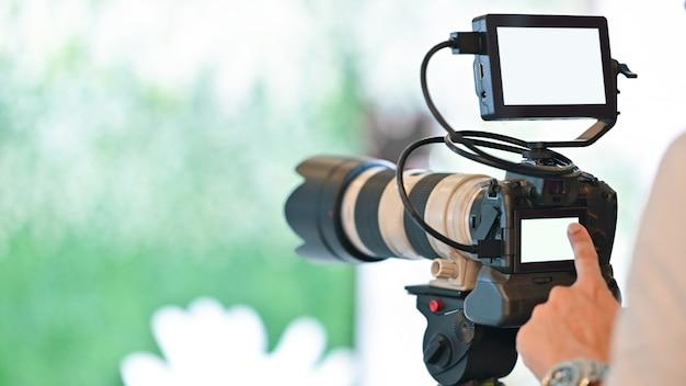 Bijgesneden opname van de vinger van de fotograaf terwijl hij naar het witte lege scherm van de videocamera van de fotograaf wijst.