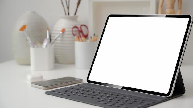 Bijgesneden opname van designer werkruimte met leeg scherm tablet, smartphone en tekengereedschappen