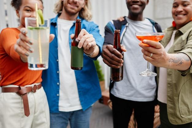 Bijgesneden opname van een diverse groep jonge mensen die genieten van een drankje op een buitenfeest op het dak, kopieer ruimte