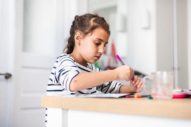 Bijgesneden opname van een gefocust klein meisje dat een foto maakt met verschillende soorten kunstbenodigdheden terwijl ze overdag aan een tafel binnen zit