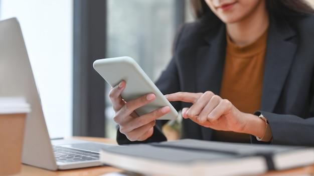 Bijgesneden opname van een gelukkige zakenvrouw die een smartphone gebruikt terwijl ze in een modern kantoor zit.