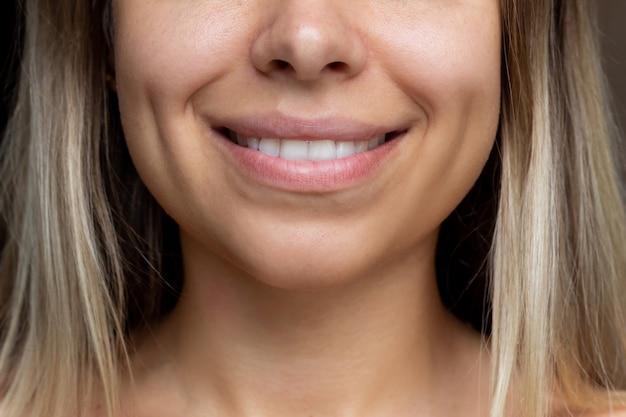 Bijgesneden opname van een gezicht van een jonge blanke lachende blonde vrouw met kuiltjes in haar wangen