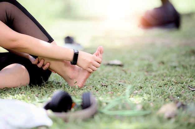 Bijgesneden opname van een jonge vrouw die haar pijnlijke voet masseert tijdens het sporten.