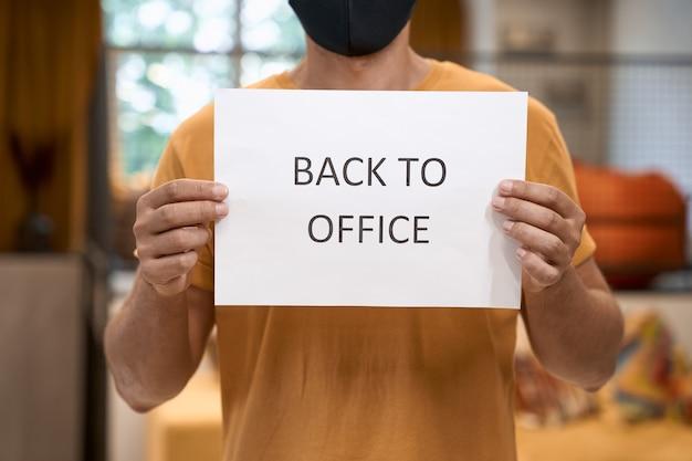 Bijgesneden opname van een mannelijke kantoormedewerker met een zwart beschermend masker met papier met tekst Premium Foto