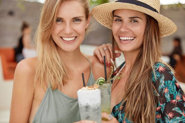 Bijgesneden opname van een mooi homoseksueel stel rust goed uit in een warm land, recreëert in een gezellig café, houdt glazen cocktails vast, heeft vrolijke uitdrukkingen. gelukkige vrouwen vieren iets op zomerfeest