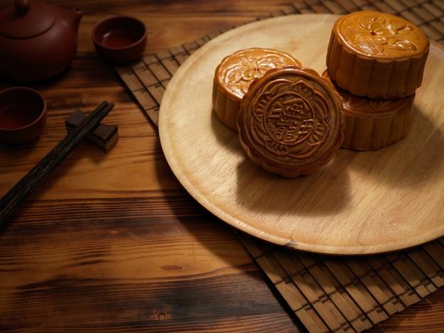 Bijgesneden opname van een plaat van traditionele maancakes op rustieke tafel. chinees karakter op de maancake vertegenwoordigt