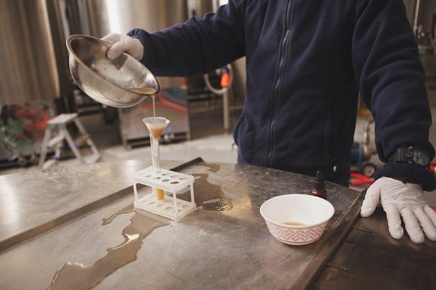 Bijgesneden opname van een professionele brouwer die kwaliteitstests uitvoert bij microbrouwerij