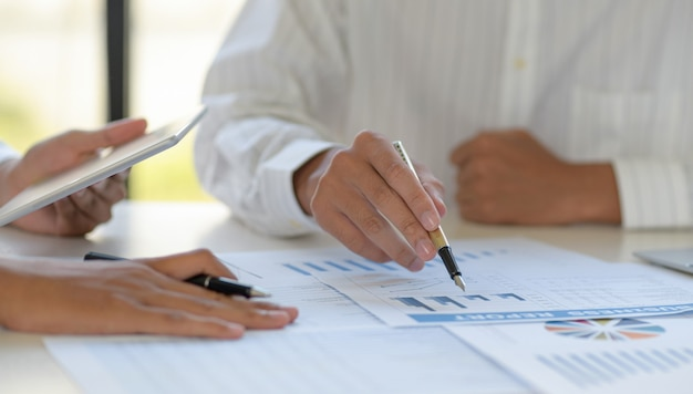 Bijgesneden opname van een team van medewerkers wijst de grafiek aan en gebruikt een tablet voor de gegevens.