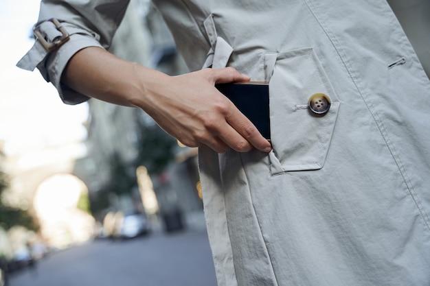Bijgesneden opname van een vrouw in grijze jas die haar smartphone in haar zak steekt terwijl ze staat