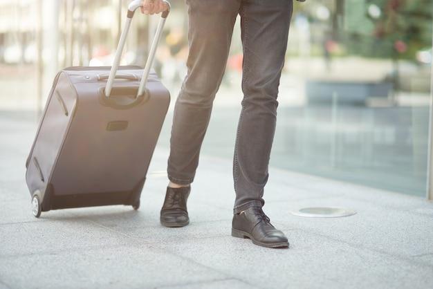 Bijgesneden opname van een zakenman die zijn koffer buiten de luchthaven trekt