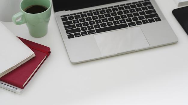 Bijgesneden opname van eenvoudige werkplek met laptop, laptops, koffiekopje en kopie ruimte