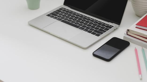 Bijgesneden opname van eenvoudige werkplek met laptop, telefoon, laptops, koffiekopje en kopie ruimte