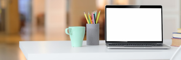 Bijgesneden opname van eenvoudige werkruimte met leeg scherm laptop, mok, briefpapier, boeken en kopie ruimte
