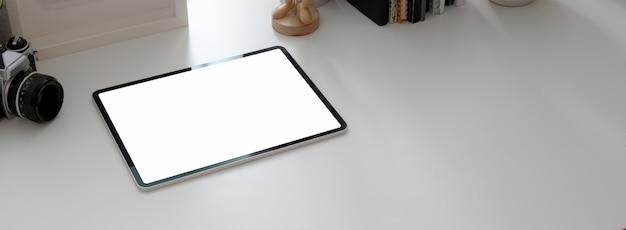 Bijgesneden opname van eenvoudige werkruimte met mock-up tablet, camera en kopie ruimte in kantoor aan huis