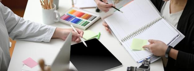 Bijgesneden opname van het brainstormen van het ontwerpteam over hun project met digitale tablet, papierwerk en designerbenodigdheden