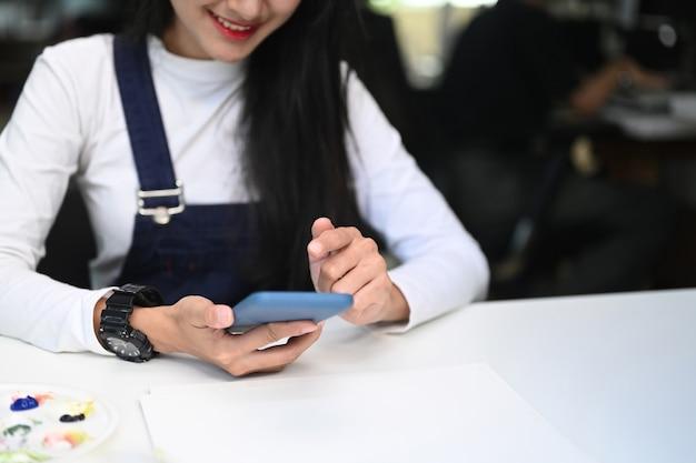 Bijgesneden opname van jonge gelukkige vrouwelijke artiest of ontwerper met behulp van slimme telefoon op haar werkstation.