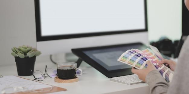 Bijgesneden opname van jonge professionele grafisch ontwerper die de kleur kiest
