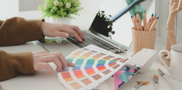 Bijgesneden opname van jonge professionele vrouwelijke ontwerper die de kleur voor haar project kiest tijdens het typen op laptop