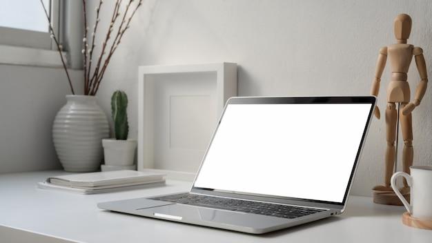 Bijgesneden opname van minimale werkplek met leeg scherm laptop, houten figuur en decoraties