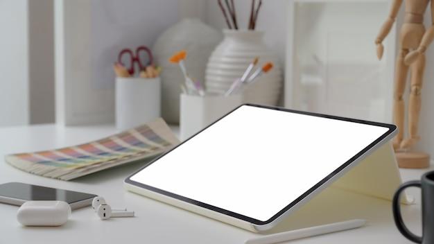 Bijgesneden opname van ontwerper met leeg scherm tablet, smartphone, draadloze hoofdtelefoon en tekengereedschappen