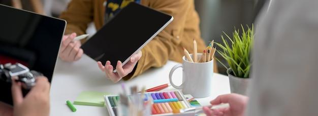 Bijgesneden opname van ontwerpteamadvies over hun project met digitale tablet, camera en designerbenodigdheden