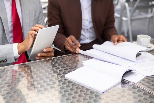Bijgesneden opname van twee ondernemers die met documenten werken