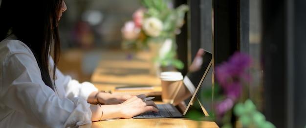 Bijgesneden opname van universiteitsstudent gericht op haar opdracht met digitale tablet