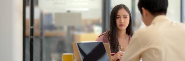 Bijgesneden opname van universiteitsstudenten die hun project raadplegen met digitale tablet