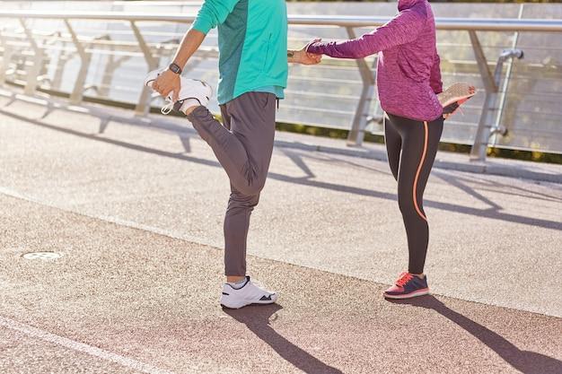 Bijgesneden opname van volwassen man en vrouw in sportkleding die de benen strekken terwijl ze samen opwarmen