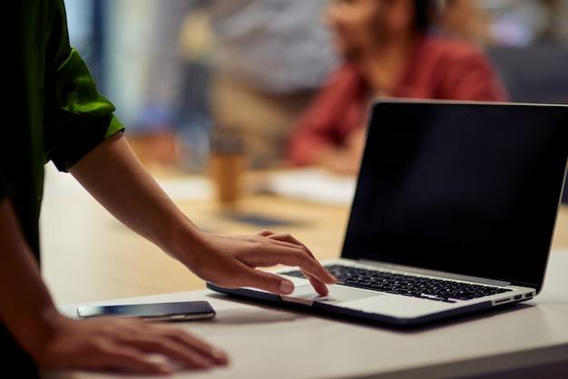 Bijgesneden opname van vrouw die laptop gebruikt terwijl ze in het moderne kantoor staat