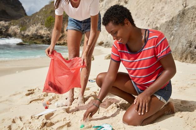 Bijgesneden opname van vrouwelijke activisten of milieuactivisten die huishoudelijk afval op het strand ophalen