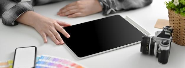 Bijgesneden opname van vrouwelijke ontwerper bezig met haar project met tablet, smartphone, camera en designerbenodigdheden