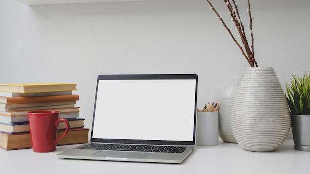 Bijgesneden opname van werkplek met leeg scherm laptop, boeken, decoraties en rode koffiekopje