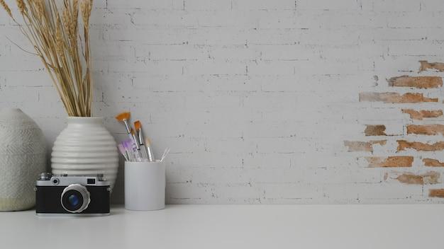 Bijgesneden opname van werkruimte met kopie ruimte, camera, schilderij borstel en keramische vazen op witte houten tafel met bakstenen muur