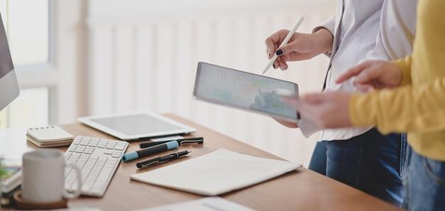 Bijgesneden opname van youngl ux-webontwikkelaar die aan haar project werkt terwijl ze een digitale tablet gebruikt