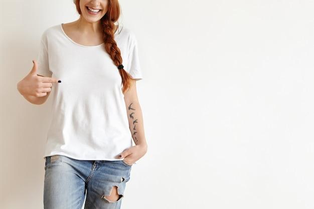 Bijgesneden portret van aantrekkelijke roodharige europese tiener met tatoeages