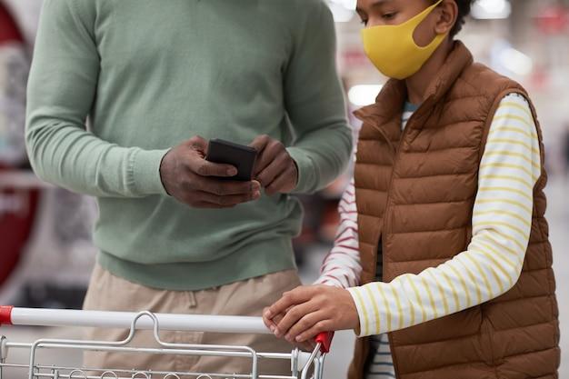 Bijgesneden portret van afro-amerikaanse vader en zoon die maskers dragen terwijl ze samen winkelen in de supermarkt en smartphone gebruiken om boodschappenlijstje te controleren