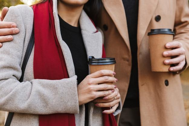 Bijgesneden portret van casual paar man en vrouw 20s afhaalmaaltijden koffie drinken uit papieren bekers