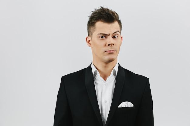 Bijgesneden portret van een jonge expressieve man in een wit overhemd en in een stijlvol zwart pak. jonge zakenman. kopieer ruimte voor uw tekst.