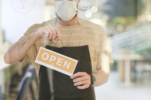 Bijgesneden portret van een jonge man met een masker terwijl hij 's ochtends een open bord op de glazen deur van het café hangt, kopieer ruimte