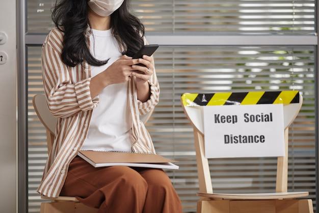 Bijgesneden portret van een jonge vrouw masker dragen en het gebruik van smartphone tijdens het wachten in de rij in kantoor met keep social distance teken, kopieer ruimte