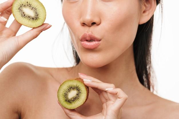 Bijgesneden portret van een mooie aziatische jonge mooie vrouw met een gezonde huid poseren geïsoleerd over een witte muur met kiwi