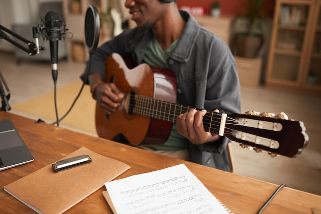 Bijgesneden portret van getalenteerde afro-amerikaanse man zingen naar microfoon en gitaar spelen tijdens het opnemen van muziek in de studio, kopie ruimte