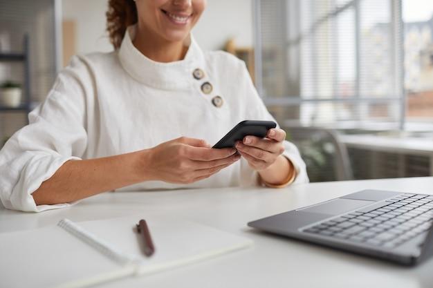 Bijgesneden portret van glimlachende zakenvrouw smartphone houden zittend aan een bureau in kantoor, kopieer ruimte